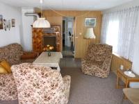 Wohnzimmer mit Couch, Kachelofen und TV